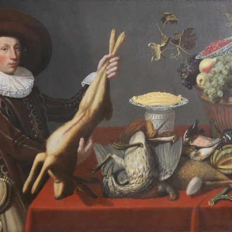 A Game Still Life with a Young Man Holding a Hare in front of a Table with other Victuals,Dutch