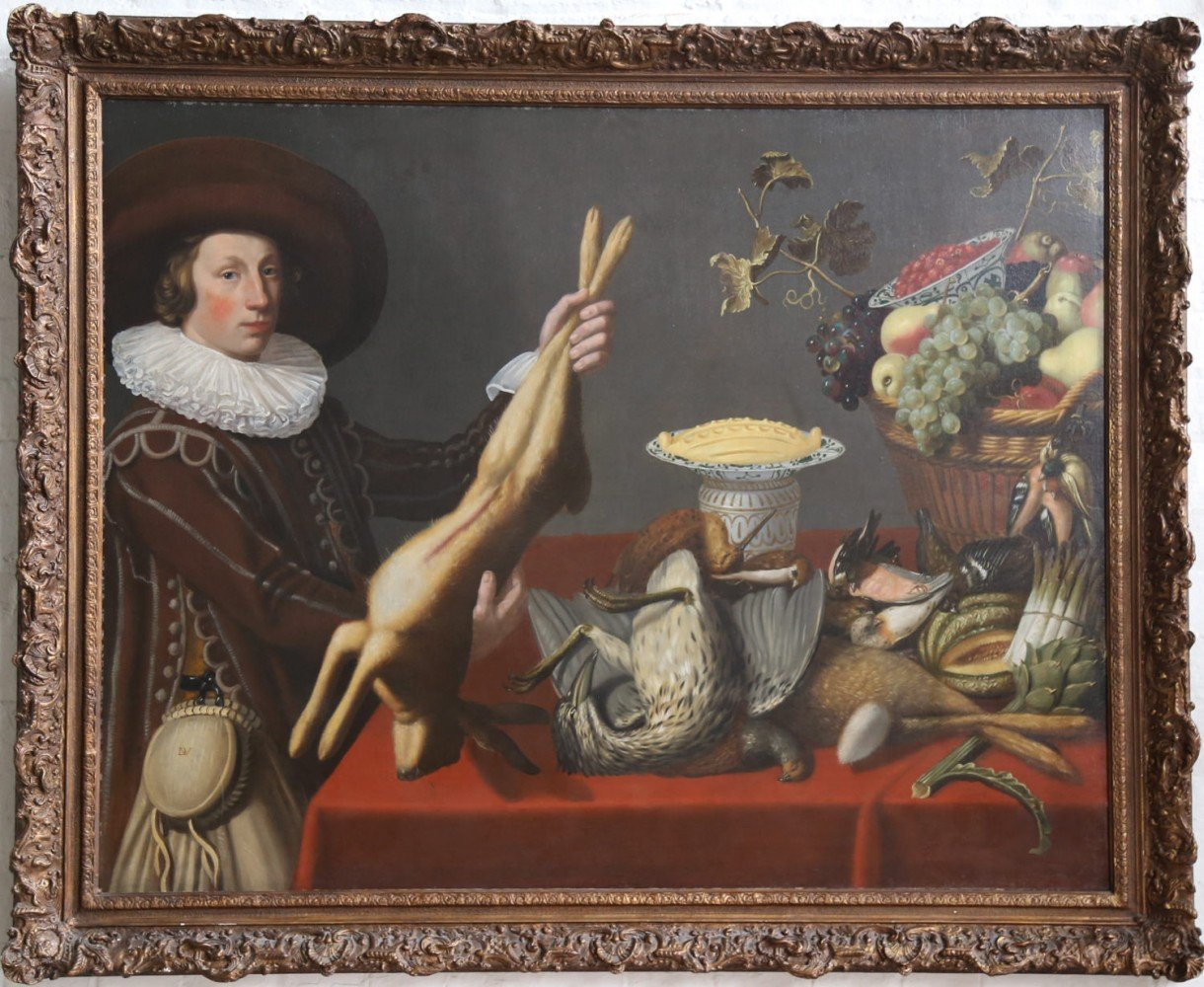 A Game Still Life with a Young Man Holding a Hare in front of a Table with other Victuals,Dutch, 1st half 17thc. by Monogrammist DV