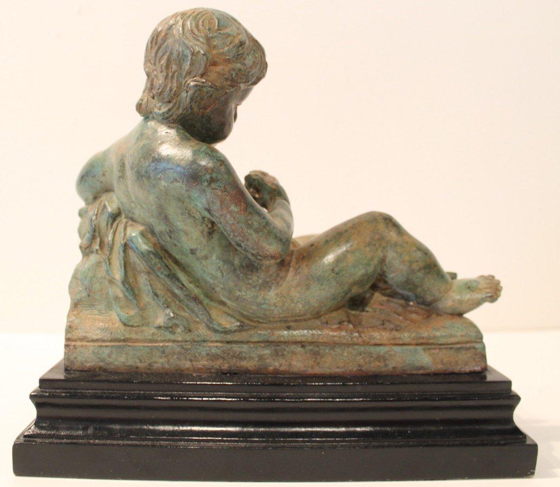 A Bronze Figure of a Reclining Cupid